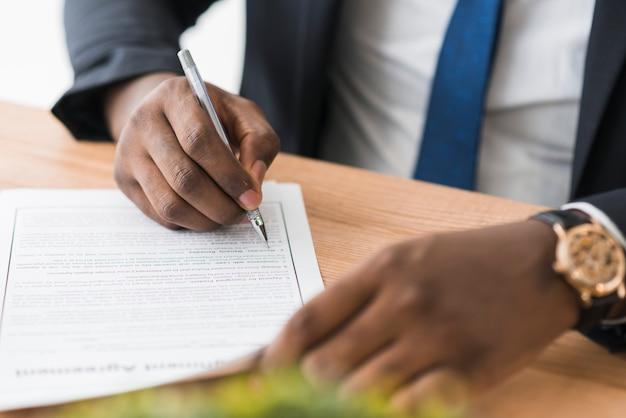 Gewas etnische zakenman ondertekening papers