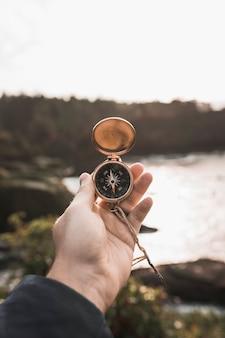 Gewas hand met kompas in de natuur