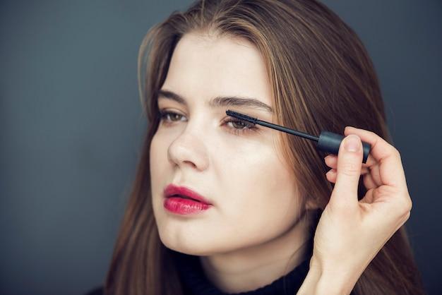 Gewas hand met mascara op model