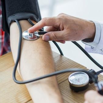 Gewas hand met stethoscoop meten van de bloeddruk