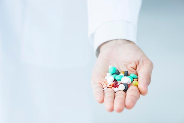 Gewas hand met verschillende pillen