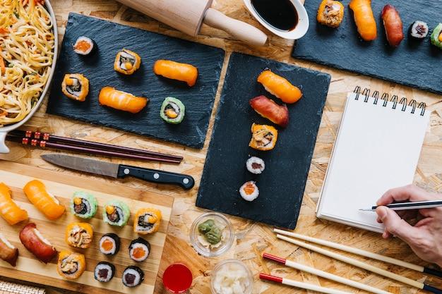 Gewas hand schrijven in een notitieblok in de buurt van sushi