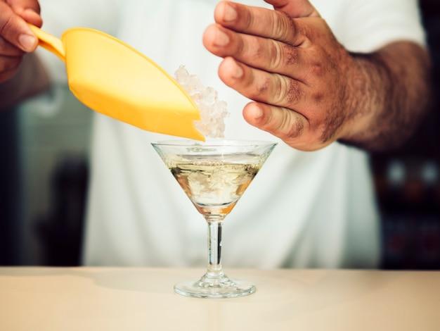 Gewas hand toevoegen van ijs in glas