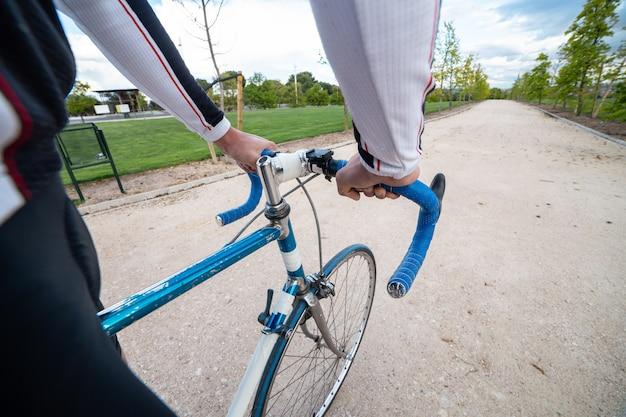Gewas handen van onherkenbaar mannelijke fietser controlerend stuur van fiets tijdens rit langs plattelandsweg