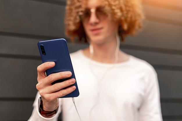 Gewas positieve jonge man met krullend rood haar in vrijetijdskleding en zonnebril met behulp van smartphone terwijl u luistert naar muziek in oortelefoons op straat in de stad