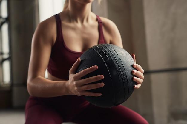Gewas sportvrouw gehurkt in de sportschool