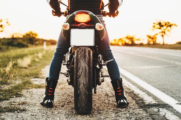 Gewas van achteraanzicht van een fietser die op zijn motorfiets zit voordat hij tegen zonsondergang aan de kant van de weg gaat.