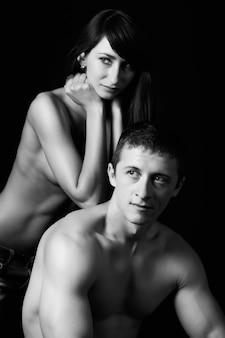 Gewas van atletische jongeman met naakte torso knuffelen charmante vriendin.