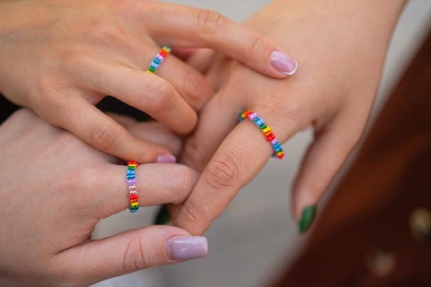 Gewas van drie meisjes die haar stijlvolle manicure tonen met hun vingers op zwart lederen handtas diff...