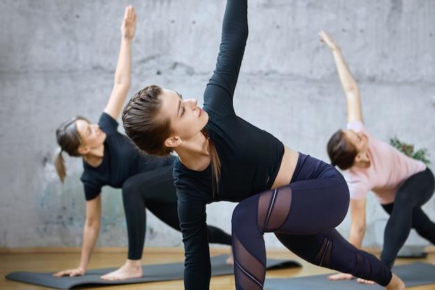 Gewas van fitnessvrouwen die het uitrekken op matten uitoefenen.
