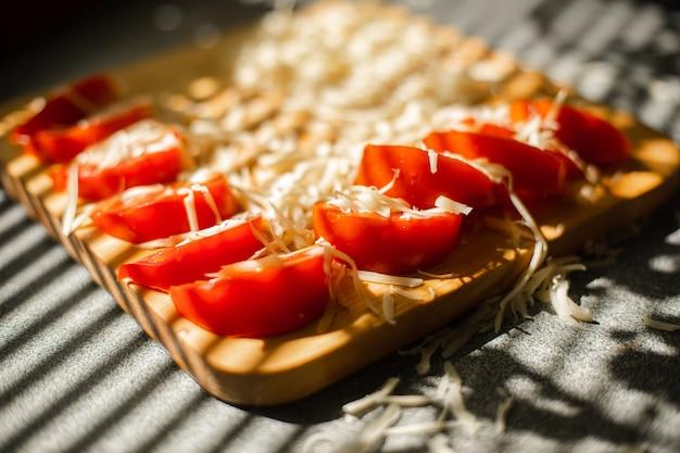 Gewas van gesneden tomaten en geraspte kaas.