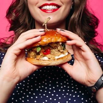 Gewas van glimlachende vrouw met rode lippen die sappige hamburger houden.