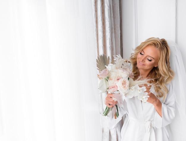 Gewas van mooie bruid; een bruidssluier dragen, een boeket vasthouden, glimlachen en zich gelukkig voelen