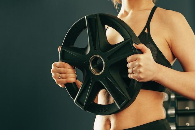 Gewas van vrouw die sportkleding dragen die oefening met domoren in gymnastiek maken
