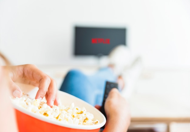 Gewas vrouw eten popcorn en kijken naar serie in de woonkamer