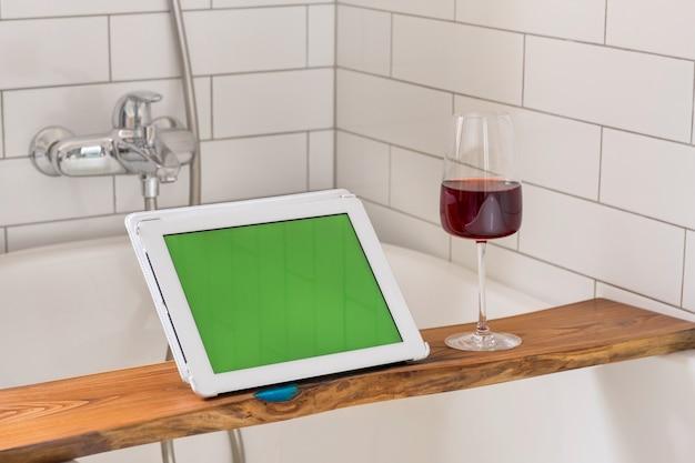 Gewas vrouw met wijn en tablet nemen bad
