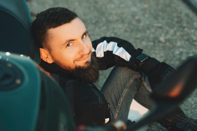 Gewas weergave van gelukkige jonge bebaarde man in biker jasje zittend op de weg leunend naar motor camera kijken