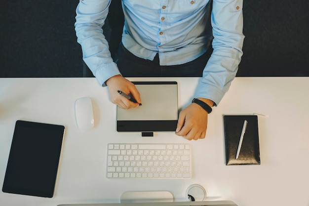 Gewas weergave van man in elegant blauw shirt zittend aan een witte tafel met computer en notebook en tekentablet van bovenaf gebruiken