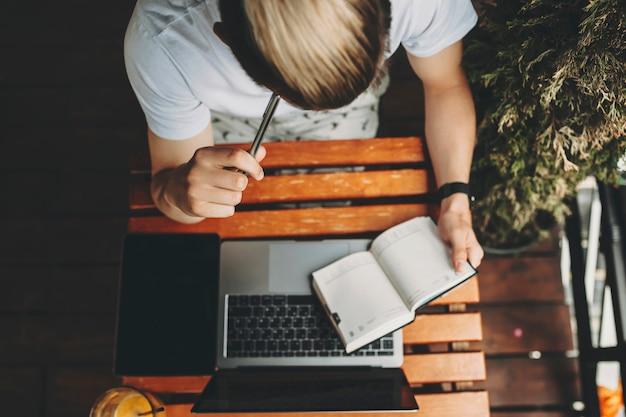 Gewas weergave van man in zomerkleren concentreren op kladblok in de hand pen naar tempel zittend aan houten tafel met laptop en tablet erop te drukken