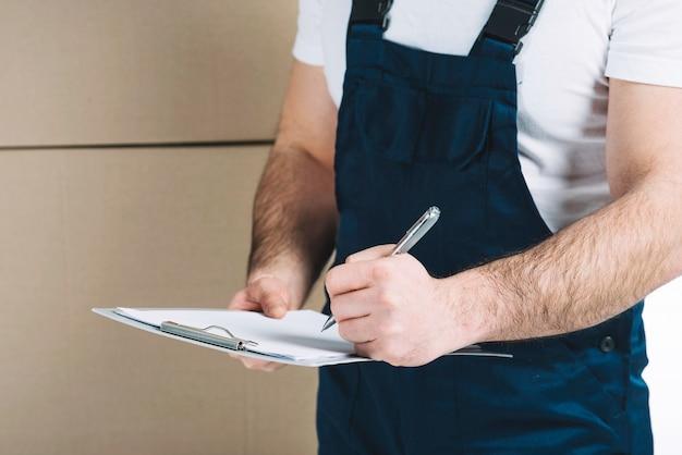 Gewaskoerier maken van aantekeningen op klembord