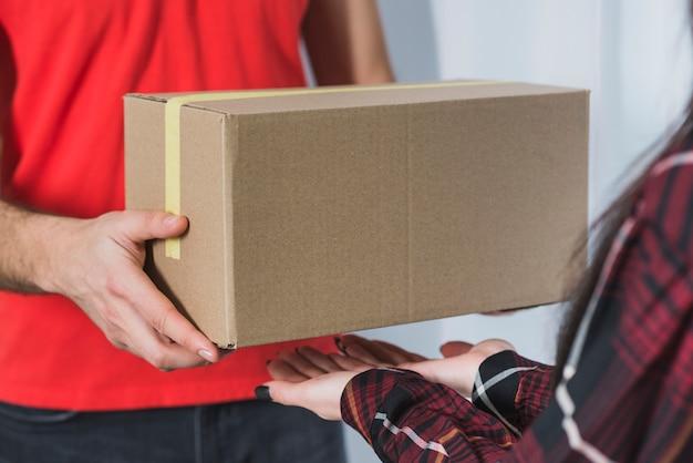 Gewaskoerier pakket aan vrouw geven
