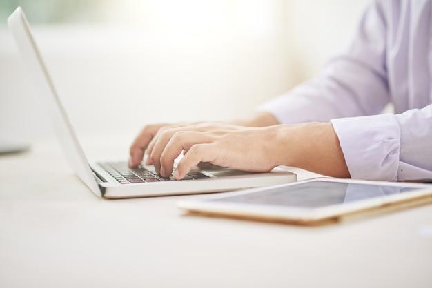 Gewassen mannelijke handen met behulp van laptop