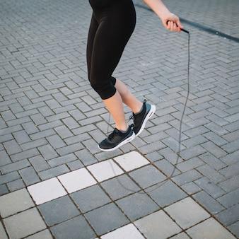 Gewassenvrouw die met kabel op straat springen
