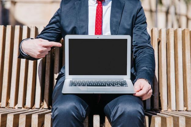 Gewassenzakenman die op laptop richten