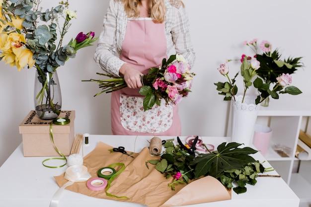 Gewasvrouw die met bloemen en document werken