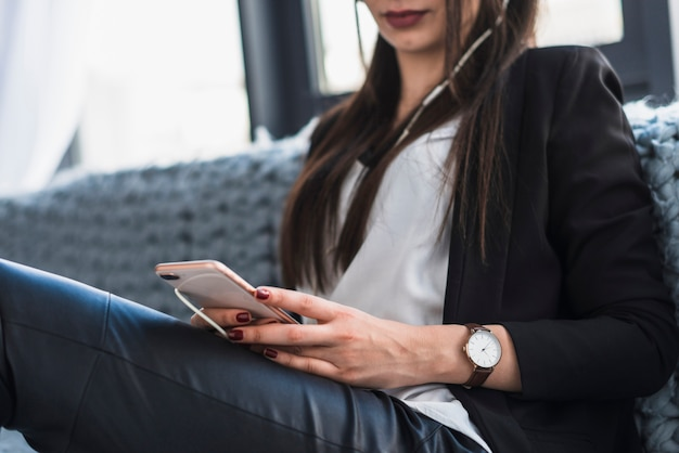 Gewasvrouw die smartphone op bank gebruiken