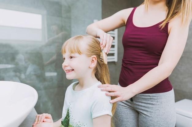 Gewasvrouw die vrolijk meisje borstelt