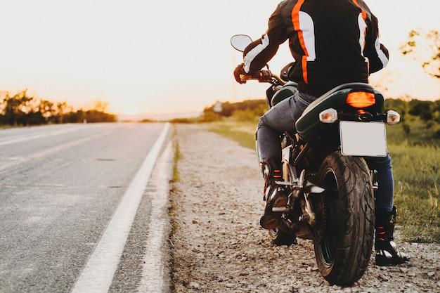 Gewasweergave van een fietser op zijn fiets vanaf de achterkant tijdens het reizen, waarbij hij zich voorbereidt om te beginnen bij de weg tegen zonsondergang in zijn avontuurlijke tijd.