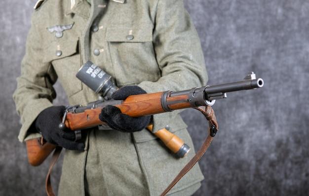 Geweer en granaat van de duitse soldaat in jas de tweede wereldoorlog