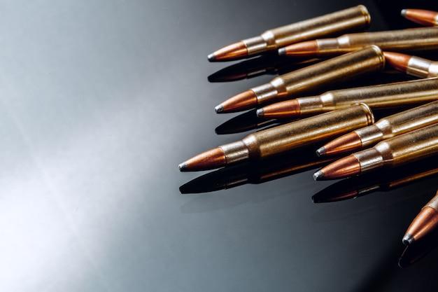 Geweerkogels of cartridges op zwarte glanzende achtergrond close-up