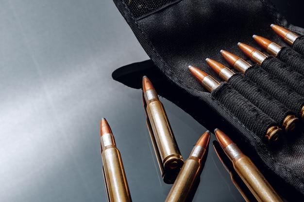 Geweerkogels of cartridges op zwarte glanzende muur close-up
