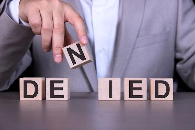 Geweigerd, het woord is geschreven op houten kubussen, blokken op de achtergrond van een man