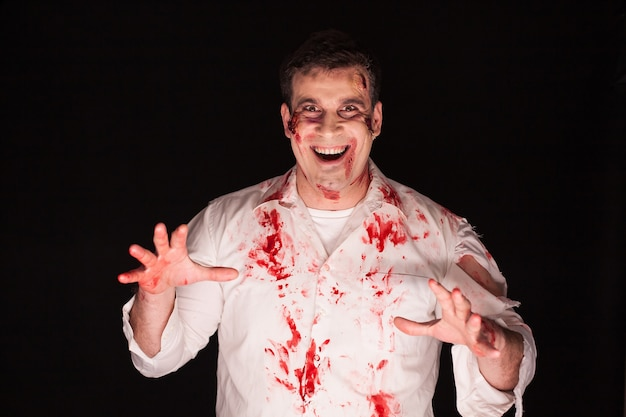 Gewelddadige en griezelige man met bloed op zijn lichaam op zwarte achtergrond.