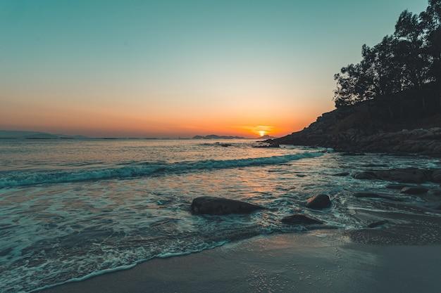 Geweldig aangelegde zonsondergang op het strand