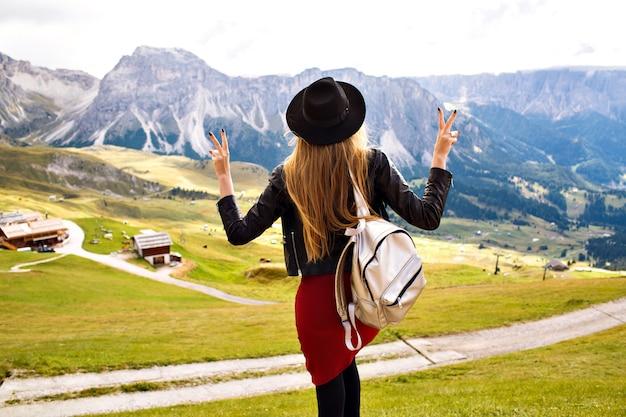 Geweldig beeld van de reiservaring van mooie stijlvolle vrouw die zich voordeed en adembenemend uitzicht op de bergen bekijkt