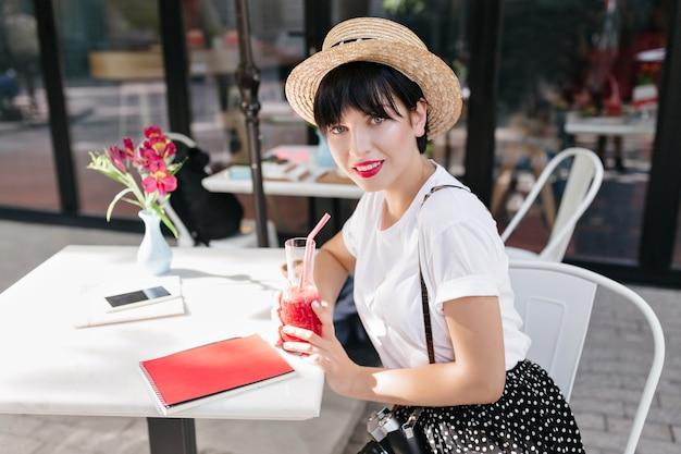 Geweldig blauwogige meisje met donker haar onder strooien hoed rusten in café aan de tafel met laptop, telefoon en bloemen erop