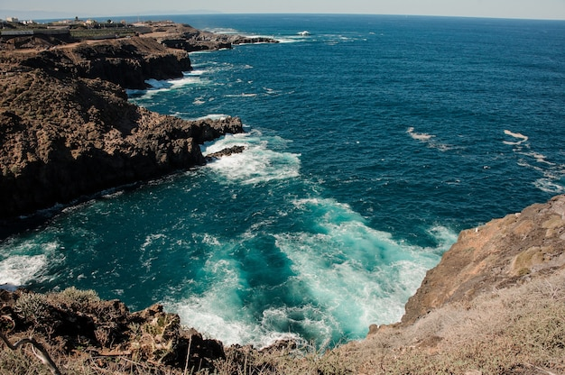Geweldig bovenaanzicht vanaf een berg van een heldere diepe zee met golven onder de heldere blauwe hemel op zonnige dag
