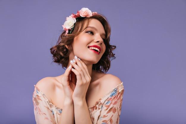 Geweldig brunette meisje in lente outfit poseren met bloemen op haar hoofd. lachende dromerige vrouw geïsoleerd.