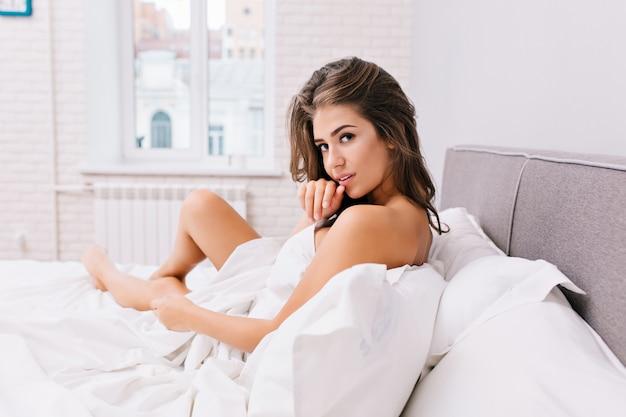 Geweldig charmant meisje met lang donkerbruin haar koelen in witte bed in modern appartement. sexy look, positieve emoties, 's ochtends wakker worden, goed humeur, mooi model.