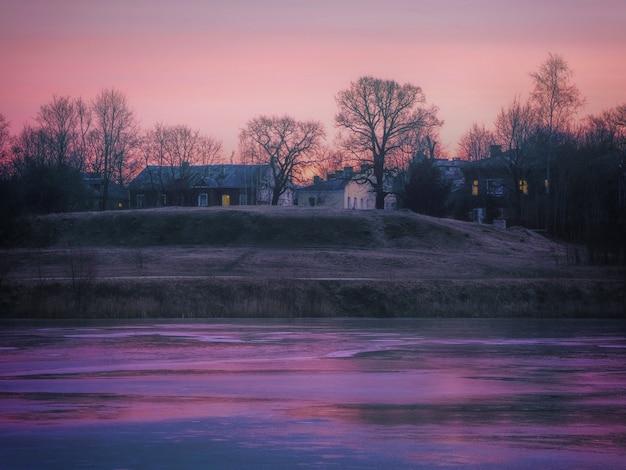 Geweldig dorp met prachtige huizen aan een kleine bevroren rivier?
