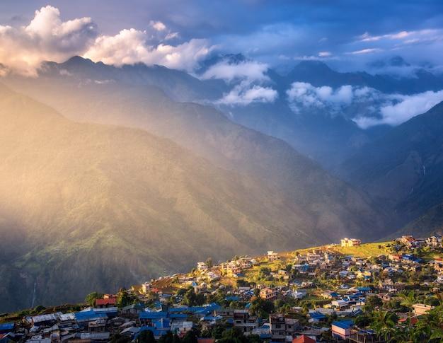 Geweldig dorp op de heuvel verlicht door een zonnestraal bij zonsondergang