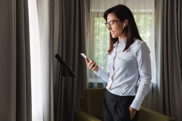 Geweldig gelukkig mooie jonge zakenvrouw in formele kleding binnenshuis thuis praten via de mobiele telefoon luisteren muziek met koptelefoon met behulp van telefoon.
