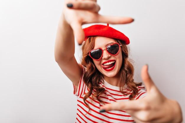 Geweldig gember meisje in zonnebril plezier tijdens fotoshoot. blij krullende vrouw in franse baret poseren op witte muur.
