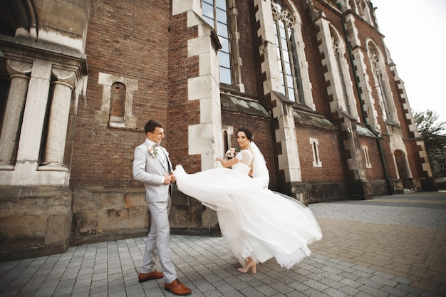 Geweldig glimlachend bruidspaar. mooie bruid en stijlvolle bruidegom in de buurt van de kerk