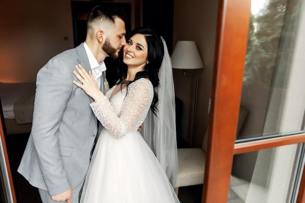 Geweldig glimlachend bruidspaar. mooie bruid en stijlvolle bruidegom.