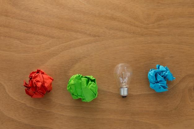 Geweldig idee concept met verfrommeld kleurrijk papier en gloeilamp